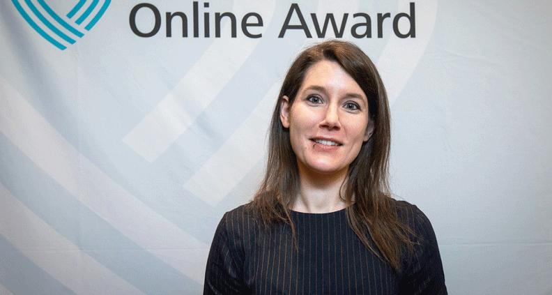 Katrin Ahäuser steht vor eine Pressewand des Grimme Online Awards