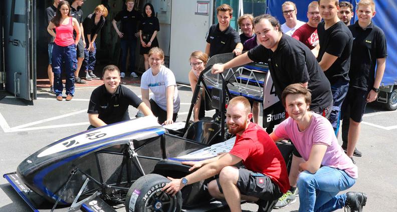 Der neue Rennwagen mit Teilen des Teams vor der Werkstatt