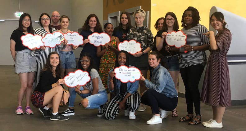 Studierende halten Schilder mit Sprüchen rund um das Klimaproblem nach oben