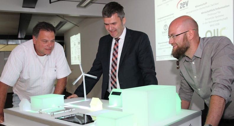 Prof. Mirko Bodach und Prof. Tobias Teich und Thomas Hempel erklären an einem Modell wie das Niederspannungsnetz umgesetzt werden soll.