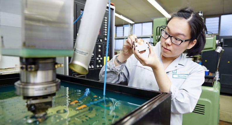 Junge Frau arbeitet in einem technischen Betrieb und trägt einen Arbeitskittel