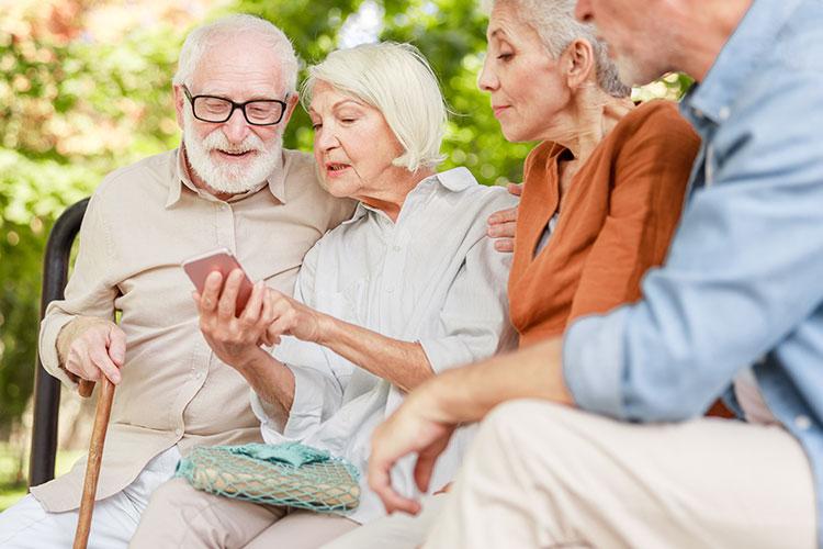 Gruppe älterer Menschen beschäftigt sich mit einem Smartphone.