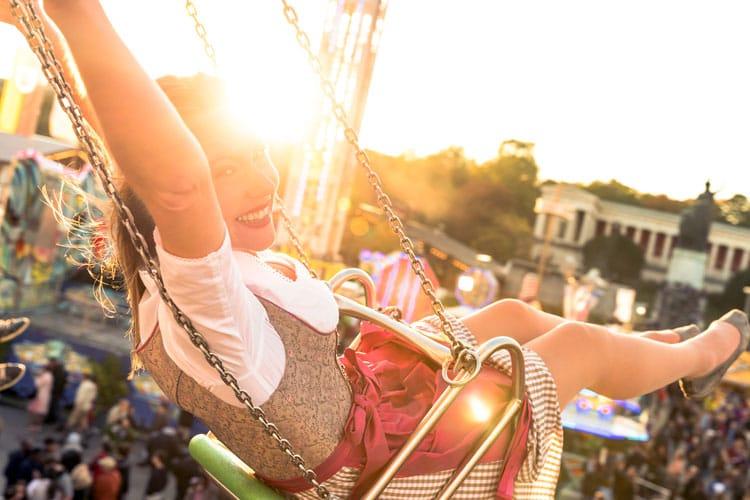 Lächelnde Frau im Dirndl auf dem Kettenkarussel des Oktoberfests