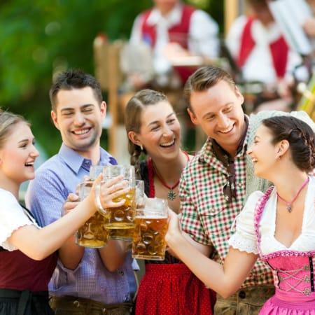 Gruppe von Freunden in Tracht auf dem Oktoberfest stoßen mit einer Maß Bier an