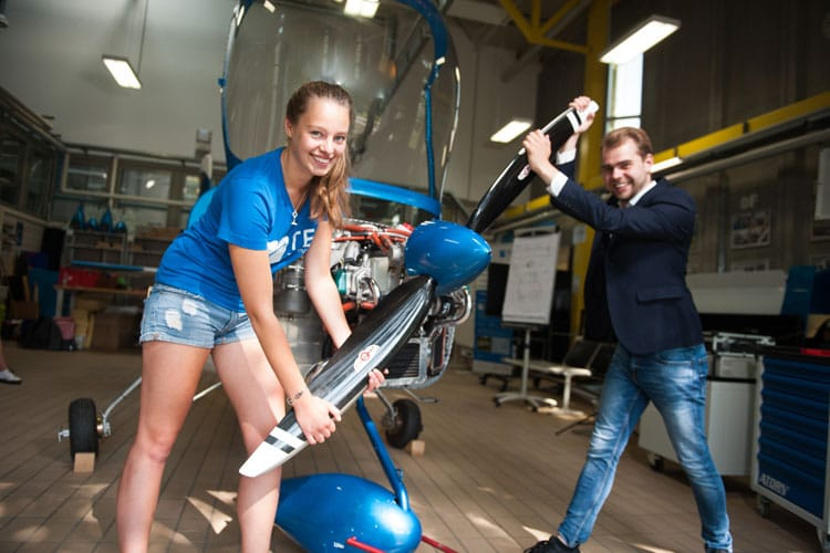 Zwei Studierende befestigen symbolisch den Propeller eines Kleinflugzeugs