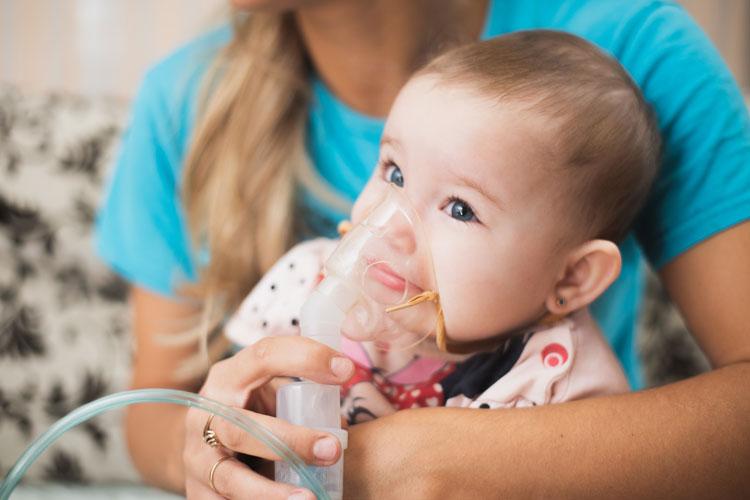 Kleinkind mit Inhaliergerät auf dem Schoß der Mutter