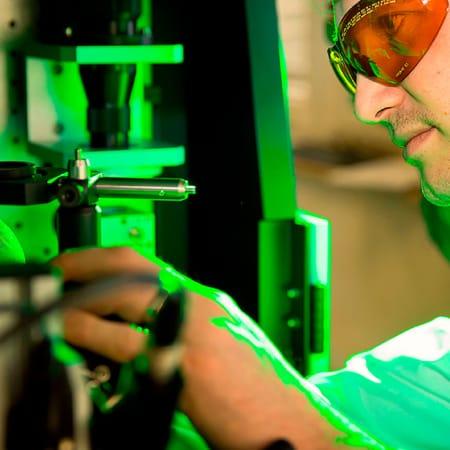 Ein Mann stellt etwas an einer Maschine im Labor ein