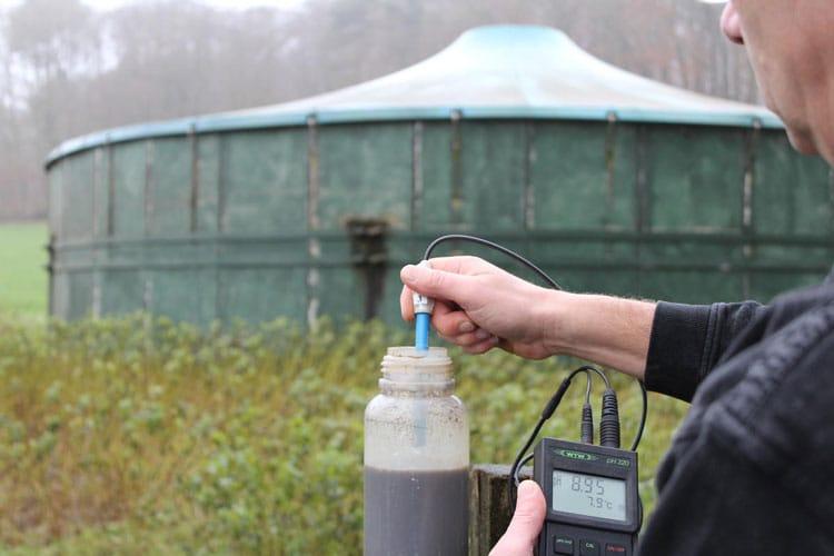 Ein Mann misst die Temperatur des Düngemittels in einer Flasche