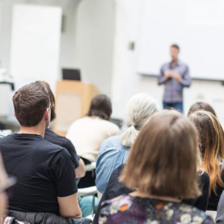 Eine Gruppe Studenten sitzen im Hörsaal bei einer Vorlesung