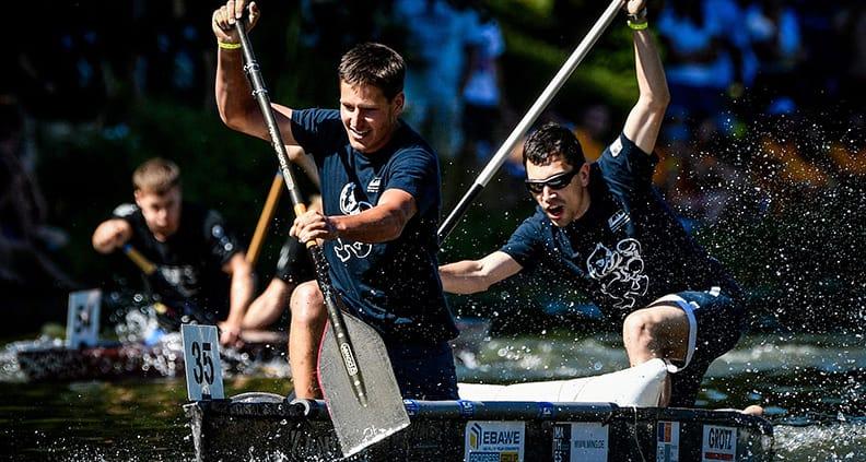 Das Männerteam steht in ihrem Kanu um kämpft um den Sieg.