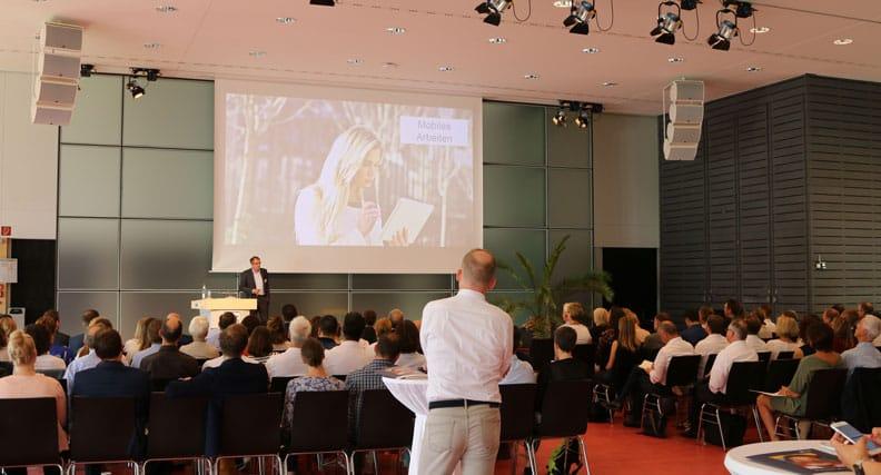 Teilnehmer der Veranstaltung sitzen in einem Konferenzsaal
