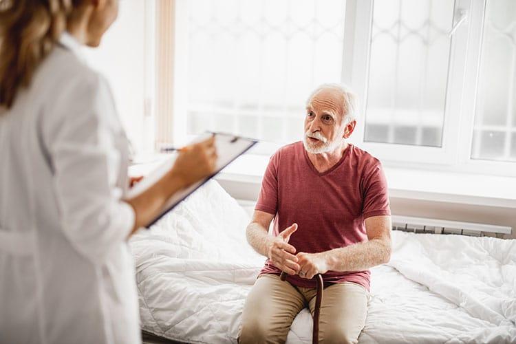 Ein älterer Mann sitzt auf dem Krankenbett, vor ihm eine Krankenschwester.
