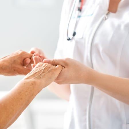 Eine Krankenschwester hält die Hand einer Patientin