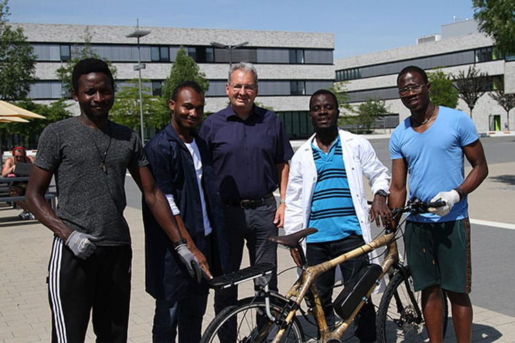 """Die ghanaischen Austauschstudierenden Harrison Tetteh (2.v.l.) und Yussif Abdullai (3.v.l.) gemeinsam mit """"Mechatronik""""-Studierenden der HSHL und Prof. Dr. Tim Wibbeke (Mitte) auf dem Campus Lippstadt"""