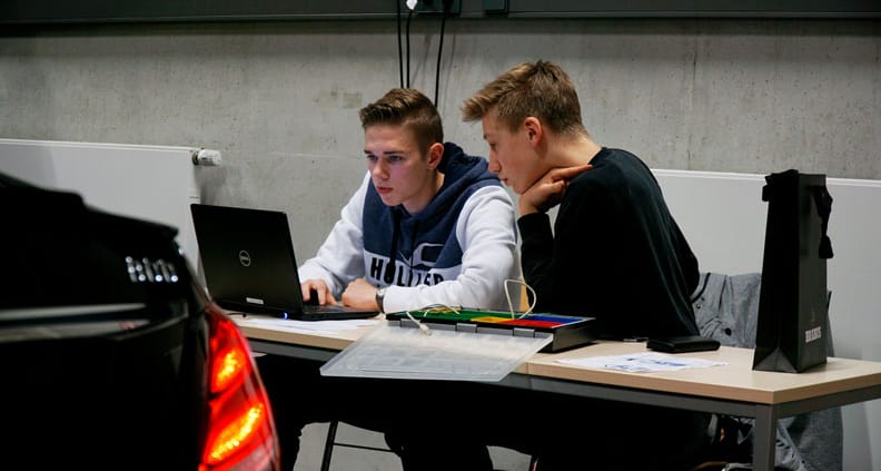 Zwei Schüler arbeiten an einem Computer in einer Montagehalle.