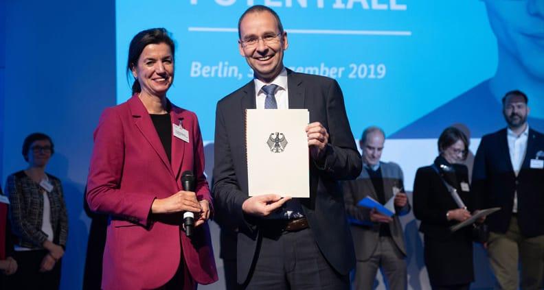 Priv.-Doz. Dr. Gerhard Heusipp vom ZFIT präsentiert stolz die Urkunde, übereicht von Dr. Sabine Hepperle vom BMWi.