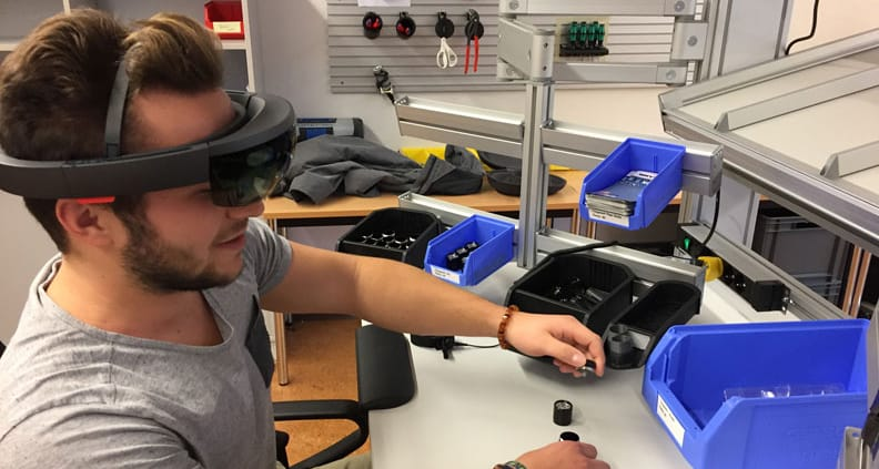 Wirtschaftsingenieurwesen-Student Sven Bunje arbeitet mit AR-Brille (Augmented Reality) am ergonomischen Arbeitsplatz.