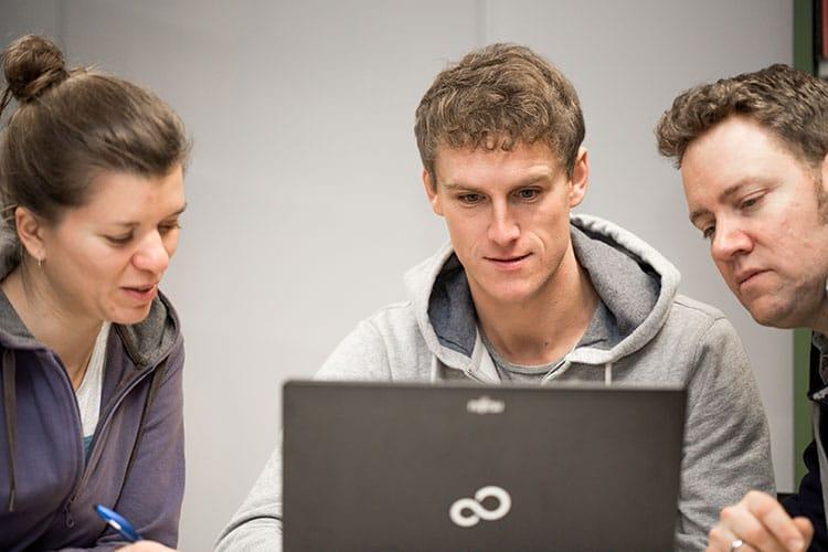 Studierende bei der Projektarbeit vor einem Laptop.