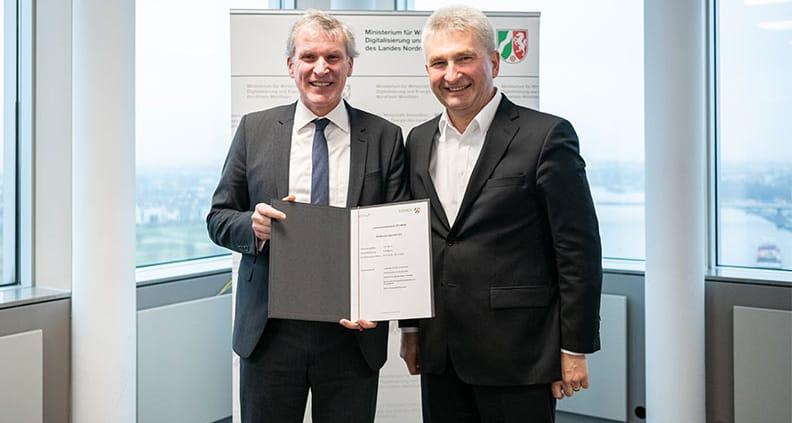 Professor Hubert Otten erhält den Förderbescheid aus den Händen von Wirtschaftsminister Professor Andreas Pinkwart.