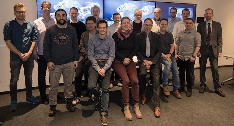 Professor Dirk Roos (vorne rechts mit grauer Krawatte) mit den Projektmitarbeiterinnen und Mitarbeitern von Hochschule Niederrhein, Siemens Gas and Power sowie Bergische Innovationsplattform für Künstliche Intelligenz.
