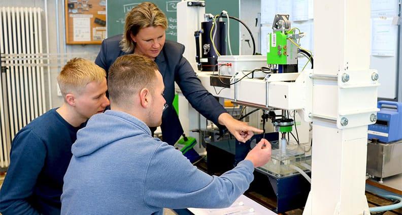 Prof. Dr.-Ing. Petra Maier erklärt Studierenden an der Werkstoffprüfmaschine das Versuchsschema.