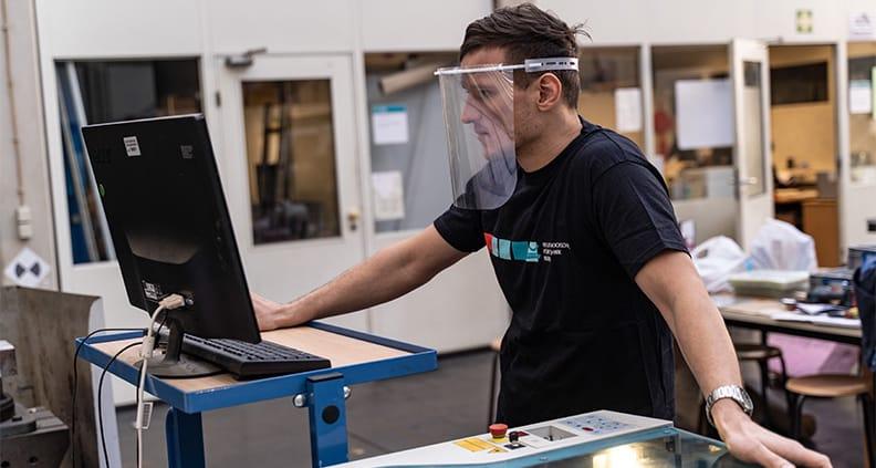 Labormitarbeiter Martin Kaiser bei der Produktion der Masken (Gesichtsschilder werden im Laser Cutter geschnitten und anschließend bearbeitet).