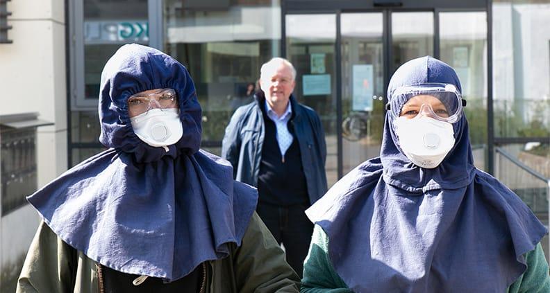 Larissa Bimberg (l.), Annika Marie Buschmann und Prof. Dr. Joachim Gardemann von der FH Münster arbeiten ehrenamtlich mit einem Helferteam daran, die Verbreitung des Coronavirus zu verlangsamen