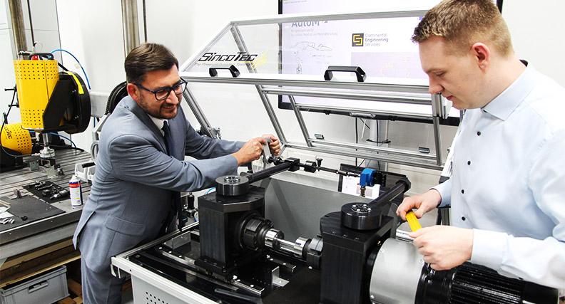 Prof. Udo Jung (links) und Doktorand Andreas Kern bereiten eine Umlaufbiegeprüfmaschine für den Test einer Werkstoffprobe vor.