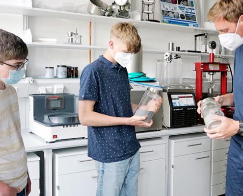 IMFAA-Mitarbeiter Benjamin Uhl zeigte im Pulverlabor wie Metalle gemahlen werden können und experimentierte mit den Schülern Johannes Memmert (links) und Benjamin Vollprecht (rechts) zum Thema additive Fertigung aus Metallen.