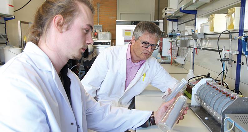 Alexander Behr (links) und Prof. Markus Röhricht begutachten im Labor zwei Kunststoffflaschen, mit denen verschmutztes Wasser desinfiziert werden kann.