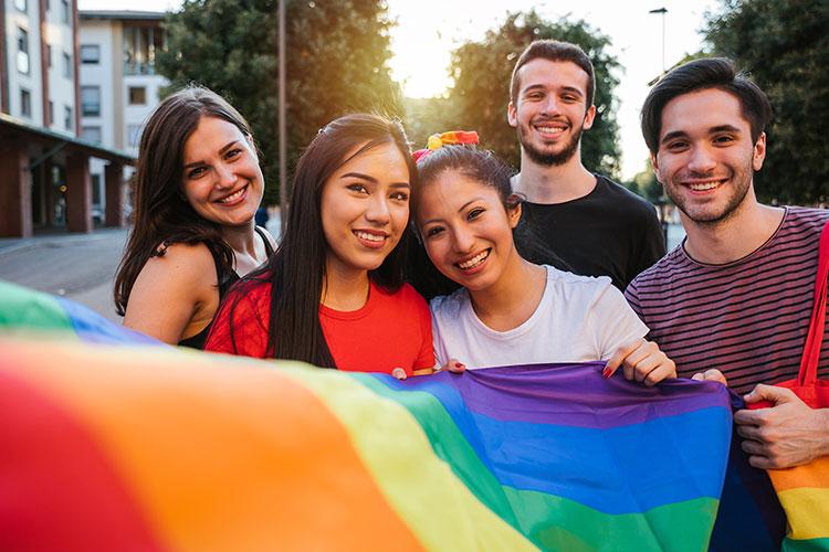 Freunde mit internationalem Background und LGBTQ-Flagge